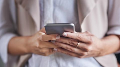 Iphone in handen van een persoon die de opslag van zijn gegevens probeert te beheren.