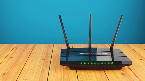 Een router geplaatst op een houten tafel voor een blauw geschilderde muur.