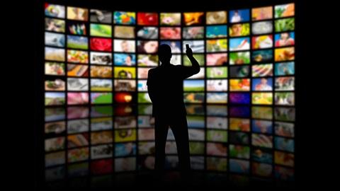 Een man kijkt op een gigantisch scherm naar een streamingaanbieding.