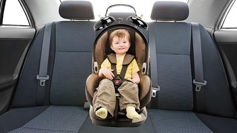 Een kind zit in een autostoel.